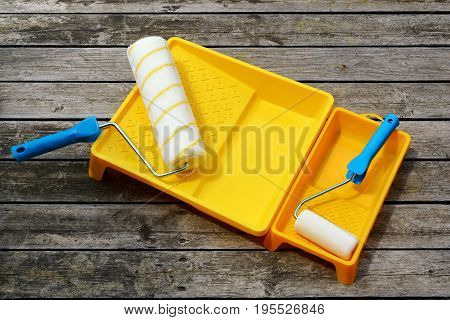Yellow Painting  Tray And Paint Roller Made Of Synthetic Fiber On The Surface Of Wooden Slats.