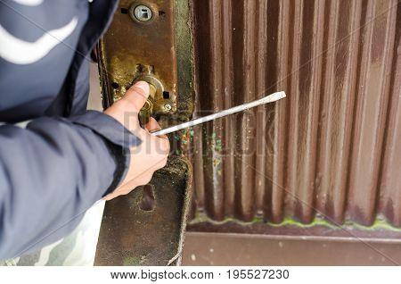 The burglar destroyed the lock on the old metal door. Selective focus.
