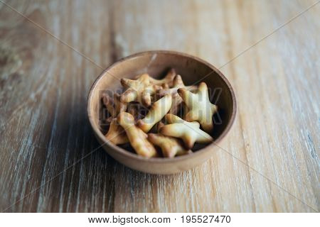 Small biscuits in many shapes in wooden cup on wood table background