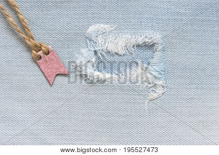 Torn denim background with tag. Blue jeans cloth texture.