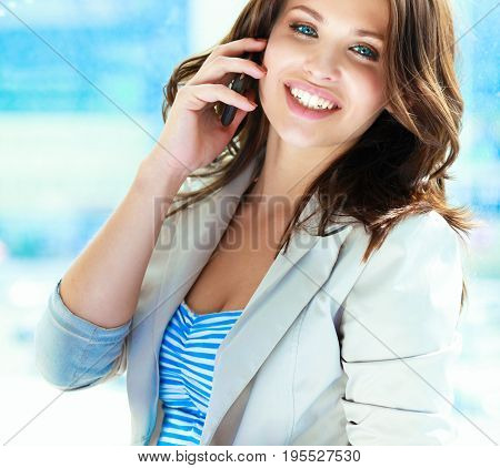 Portrait of young businesswoman with mobile phone on office hallway.