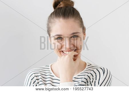 Beautiful Green-eyed European Female In Casual Clothes Looking At Camera, Smiling, Touching Mouth Wi