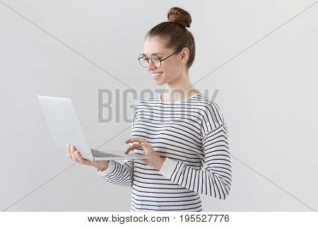 Indoor Photo Of Positive Teenage Girl Isolated On Grey Background Standing With Laptop, Smiling At G