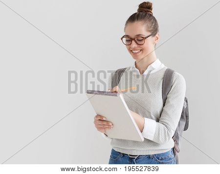 Indoor Shot Of Young European Female On Right Side Of Photo Against Gray Background Taking Notes On