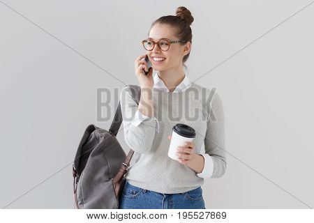 Studio Photo Of Student Girl Isolated On Grey Background With Backpack On Her Back, Holding Takeaway