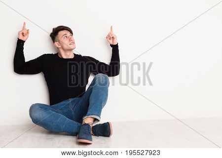 Young man points up, copy space at white studio background