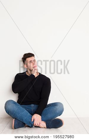 Pensive young man looks up, sitting on the floor at white background, copy space