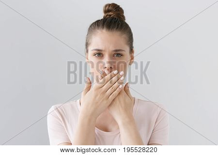Horizontal Photo Of Young European Female Isolated On Gray Background With Expression Of Secrecy And