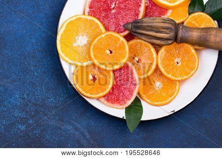 Fresh oranges, grapefruits and madarine slices on dark blue stone background. Rustic kitchen utensils: wooden squeezer. Top view with copy space