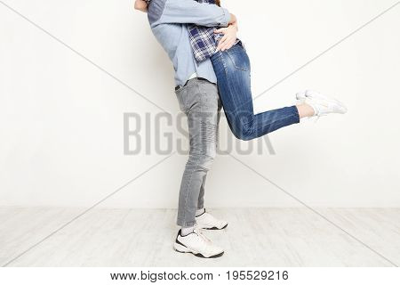Loving couple at white isolated studio backgroung. Man holding woman in his arms, crop
