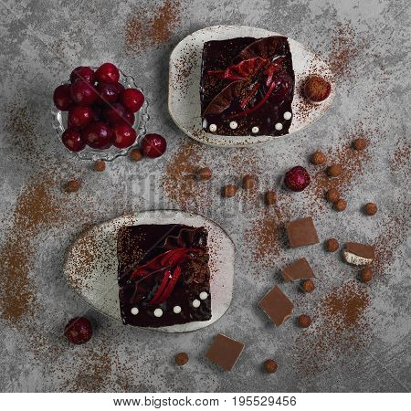Chocolate cheesecake layered brownies cakes with with dark cherries and cherry sauce. Ingredients for Chocolate cherries cakes Pieces of chocolate and fresh cherries. Gray stone background. Top view.