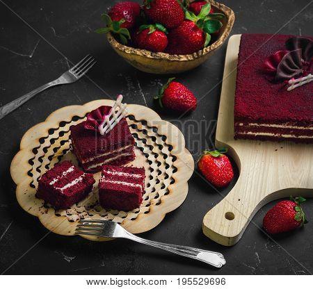 Close-up red velvet cake and white cream on wooden plate. Whole red velvet cake on wooden board.  Fresh strawberries on dark black background.