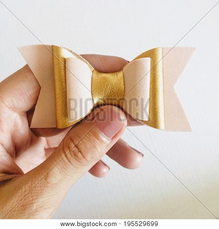 Hair bow in hand on a white background