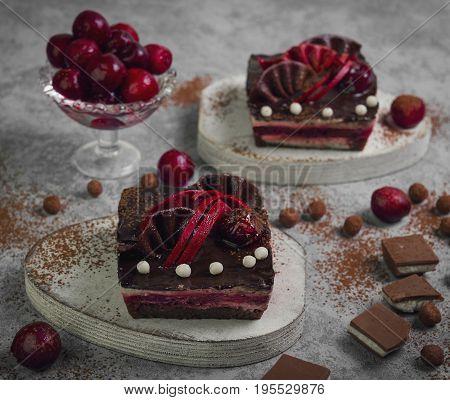 Chocolate cheesecake layered brownies cakes with with dark cherries and cherry sauce. Ingredients for Chocolate cherries cakes Pieces of chocolate and fresh cherries. Gray stone background.