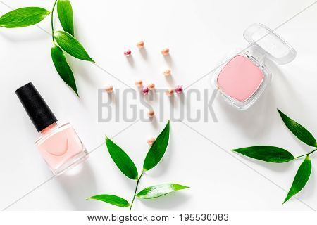 Blush and nail polish on white table background top view.
