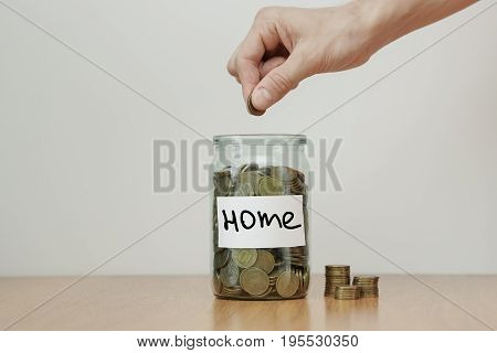 Distribution Of Cash Savings Concept. Hand Puts Coins To The Glass Money Boxes With Inscription 'hom