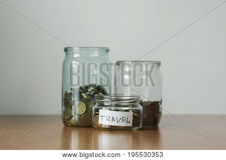 Coins In Glass Jars For Different Needs, Money Boxes. Distribution Of Cash Savings Concept. Travel S