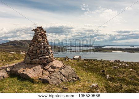 Assynt Peninsula Scotland - June 7 2012: stone pile marker above Altandhu hamlet on Atlantic Ocean inlet shore with multitude of rocky islets under heavy storm sky.