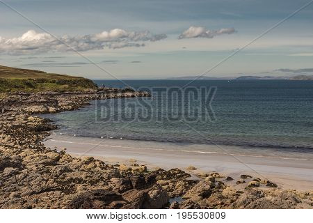 Assynt Peninsula Scotland - June 7 2012: Enard Bay and Atlantic Ocean under clear sky with a few white clouds. Rocky foreground and small sandy beach.