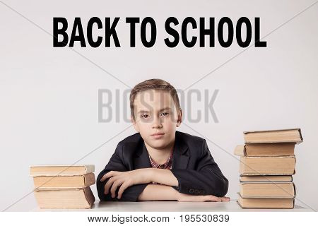 Pupil In Suit At His Desk On Grey Background With Books. Inscription 'back To School'.