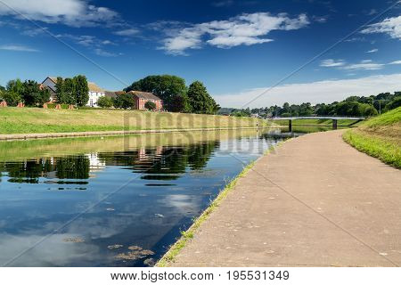 View of the Exe River Canal in Exeter. Sunny calm morning. You can see a car bridge through the canal. Exeter. Devon. England