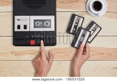 Retro stuff old items memories. Hands switching on old tape cassette recorder and holding three cassettes choosing which song to reproduce. Woman listening to old songs remebering her youth