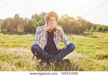 Pensive Teenager Sitting Outdoors At Field Admiring Picturesque Landscapes Thinking About Something