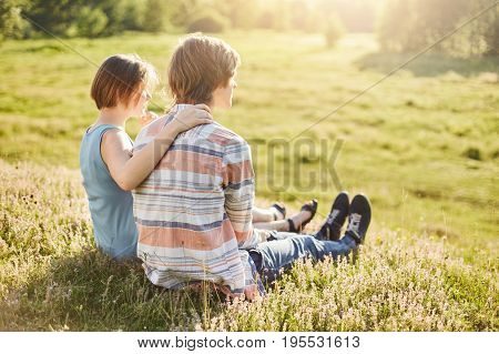 Sweet couple of teenagers sitting outdoors on greenland embracing admiring fresh air and sunlight having talk sitting backs. Cute girl and boy in love spending their free time together outdoors