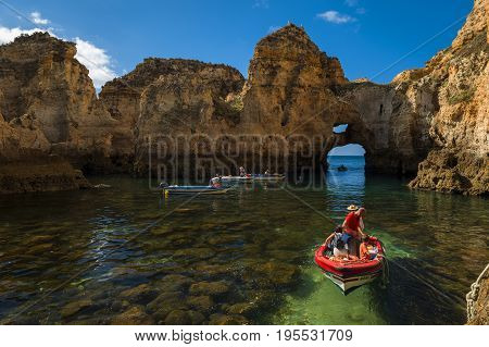Ponta da Piedade Portugal - July 6 2017: Boats in the small bay between the sandstone cliffs at the Ponta da Piedade in Lagos Portugal