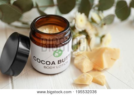 Beautiful composition with jar of cocoa butter lotion on table