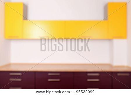 Interior of modern kitchen with empty bright furniture, blurred view
