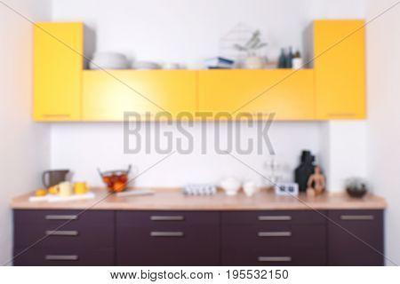 Interior of modern kitchen with bright furniture, blurred view