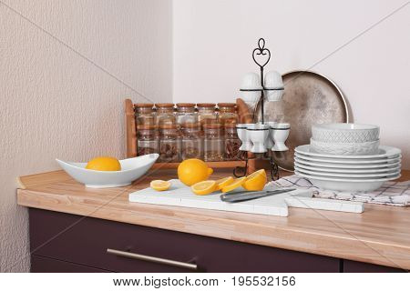 Composition with sliced lemon, crockery and set of spices on counter in kitchen