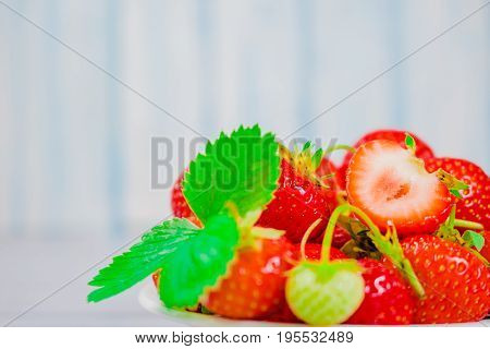 strawberries in bowl on wooden background with copy space and low key.