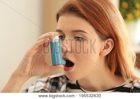 Young woman using inhaler for asthma and respiratory diseases at home