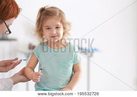 Doctor vaccinating child on light background