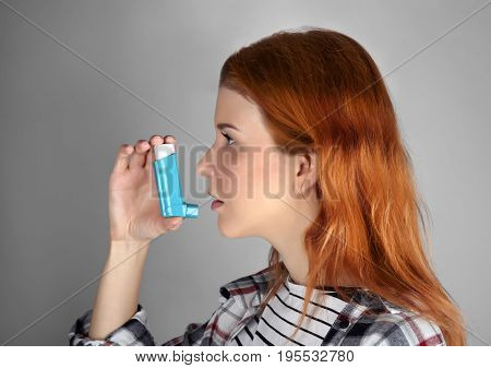 Young woman using inhaler for asthma and respiratory diseases on light background