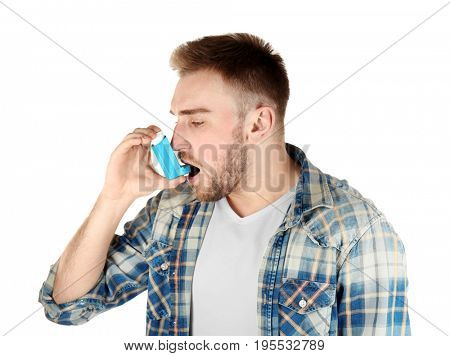 Young man using inhaler for asthma and respiratory diseases on white background
