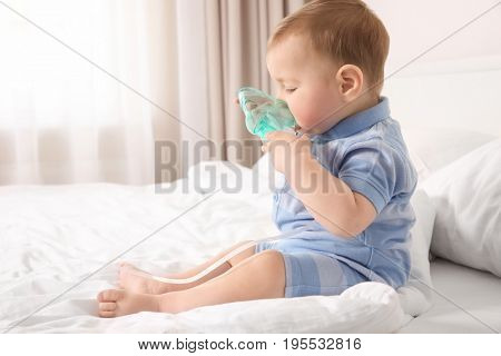 Cute little baby with nebulizer sitting on bed at home. Health care concept