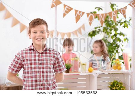Cute little boy and blurred stand with lemonade on background