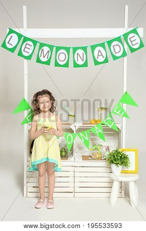 Cute little girl standing near counter with lemonade on white background