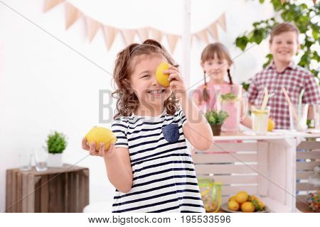 Cute little girl holding lemons and blurred stand with kids on background