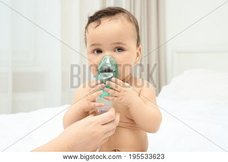 Mother using nebulizer for cute little baby sitting on bed at home. Health care concept