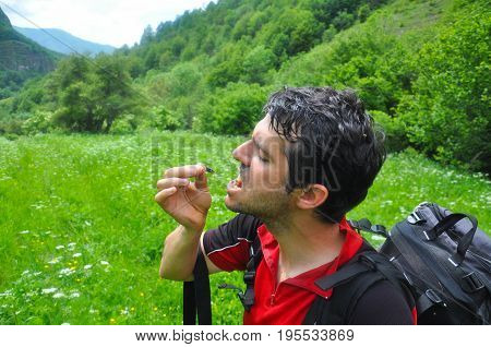 Men eating a grasshopper. Extreme survival in a nature