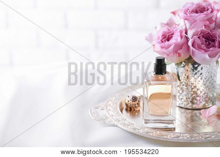 Metal tray with bottle of perfume and flowers on light background