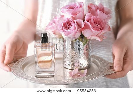 Woman holding metal tray with bottle of perfume and flowers