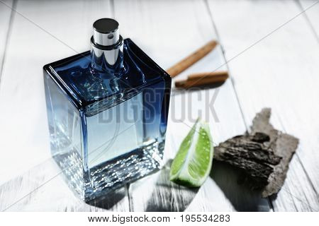 Composition with modern male perfume on wooden background