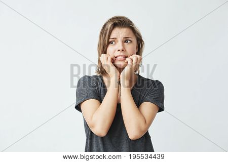 Nervous young beautiful girl holding hands on cheeks over white background. Copy space.