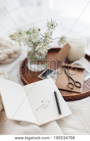 Wooden tray with paper notebook, old photos, candle and spring flowers on white bedding. Relaxing, or working, or writing diary or blog in bed at home.