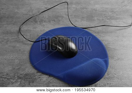 Blank mat and computer mouse on textured background